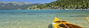 A yellow kayak sits on the beach in Lake Tahoe facing the water.